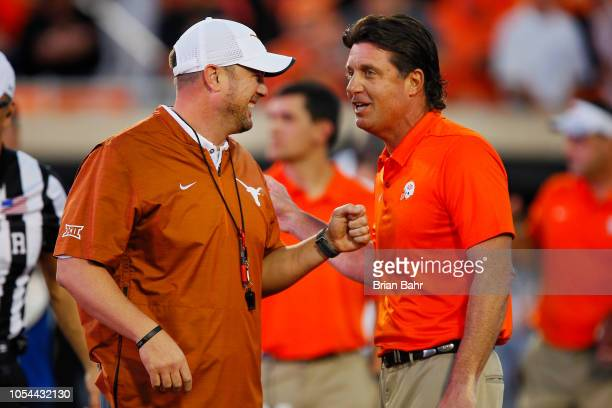 Head coach Tom Herman of the Texas Longhorns greets head coach Mike Gundy of the Oklahoma State Cowboys before their game on October 27 2018 at Boone...