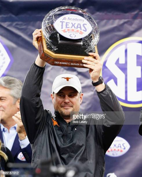 Head coach Tom Herman of the Texas Longhorns holds up The Robert C McNair Trophy after defeating Missouri Tigers 3316 in the Academy Sports Outdoors...