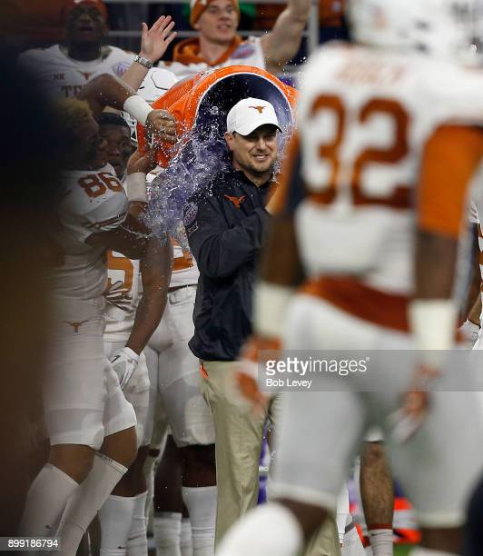 Head coach Tom Herman of the Texas Longhorns is doused by his players after defeating the Missouri Tigers 3316 at NRG Stadium on December 27 2017 in...