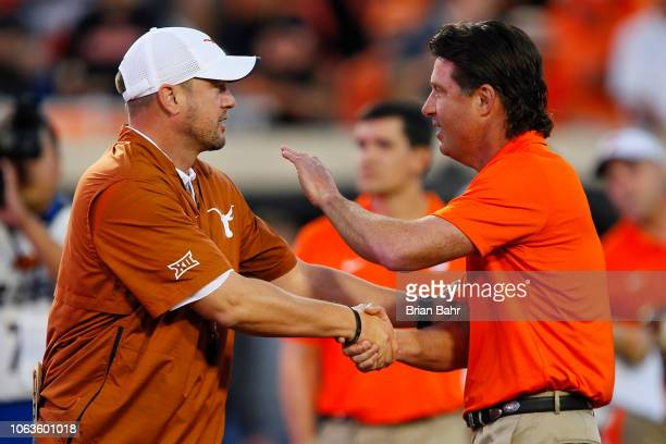 Head coach Tom Herman of the Texas Longhorns shakes hands with head coach Mike Gundy of the Oklahoma State Cowboys on October 27 2018 at Boone...