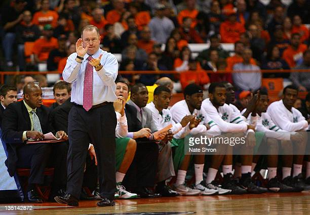 Head coach Tom Herrion of the Marshall Thundering Herd claps from the sideline during the game against the Syracuse Orange at the Carrier Dome on...