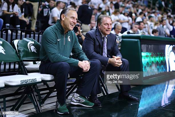 Head coach Tom Izzo of the Michigan State Spartans and football head coach Mark Dantonio of the Michigan State Spartans sit on the bench prior to the...