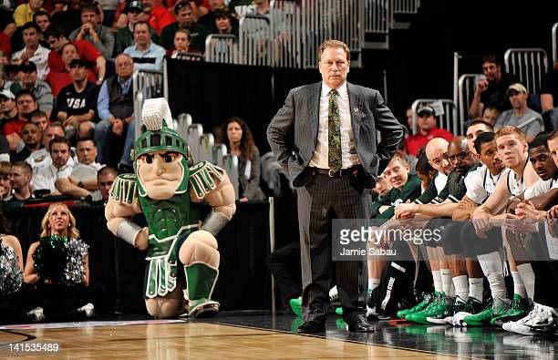 Head coach Tom Izzo of the Michigan State Spartans and the Michigan State Spartans mascot look on during the first half against the St Louis...