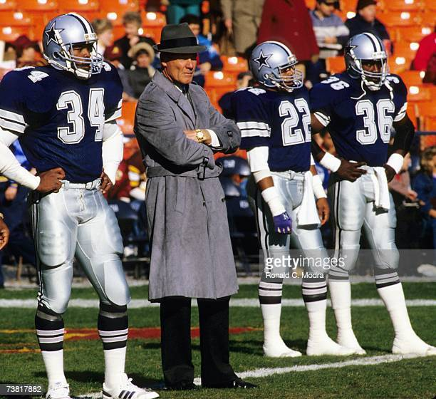 Head Coach Tom Landry of the Dallas Cowboys flanked by players Herschel Walker Victor Scott and Vince Albritton on the sidelines during a game...