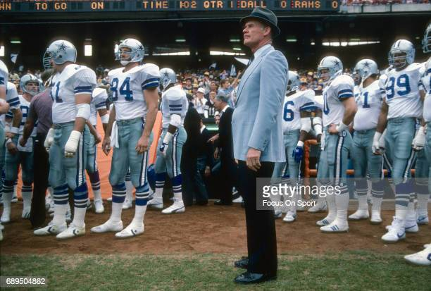 Head coach Tom Landry of the Dallas Cowboys stands with his players prior to the start of an NFL football game against the Los Angeles Rams circa...