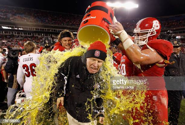 Head coach Tom O'Brien of the North Carolina State Wolfpack is dunked in Gatorade after defeating the Louisville Cardinals 3124 at Bank of America...