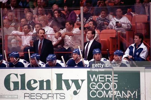 Head coach Tom Watt and assistant coach Mike Kitchen and equipment manager Brian Papineau stand behind the Toronto Maple Leafs bench against the Los...