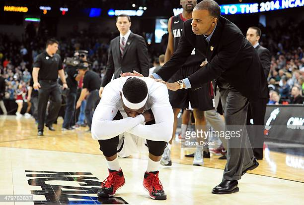 Head coach Tommy Amaker of the Harvard Crimson consoles Justin Jackson of the Cincinnati Bearcats after Harvard won their second round of the 2014...