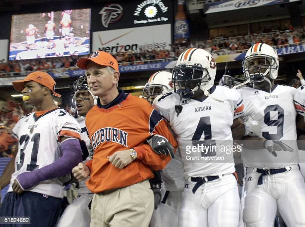Head coach Tommy Tuberville of the Auburn Tigers leads his team onto the field against the Tennessee Volunteers in the 2004 SEC Championship Game at...