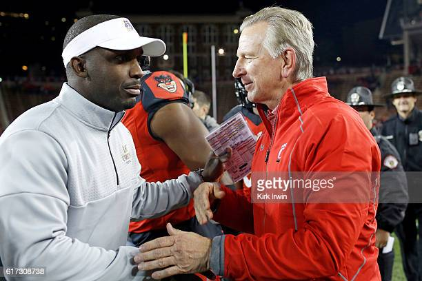 Head Coach Tommy Tuberville of the Cincinnati Bearcats shakes hands with Head Coach Scottie Montgomery of the East Carolina Pirates after defeating...