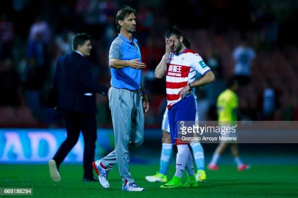 Head coach Tony Adams of Granada CF comforts his palyers as Gabriel Silva reacts after the La Liga match between Granada CF and Real Club Celta de...