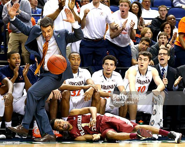 Head coach Tony Bennett of the Virginia Cavaliers moves out of the way as Devon Bookert of the Florida State Seminoles goes after a loose ball during...