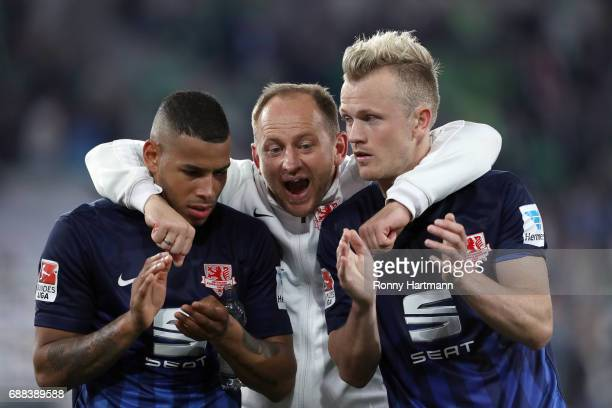 Head coach Torsten Lieberknecht of Braunschweig hugs Onel Hernandez and Nik Omladic of Braunschweig after the Bundesliga Playoff first leg match...