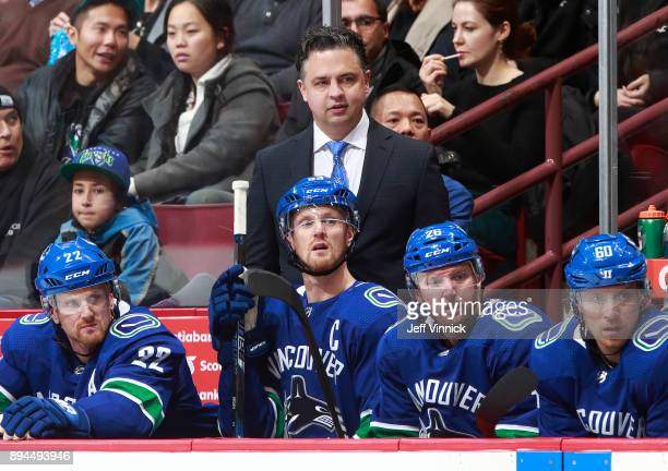 Head coach Travis Green of the Vancouver Canucks looks on from the bench during their NHL game against the Calgary Flames at Rogers Arena December 17...