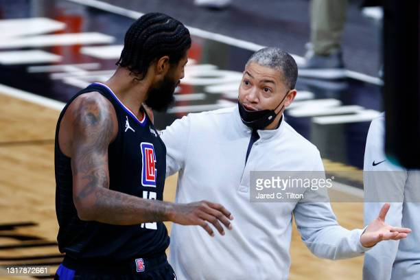 Head coach Tyronn Lue of the LA Clippers speaks with Paul George under a timeout during the second quarter of their game against the Charlotte...