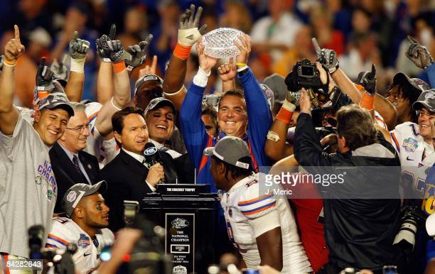 Head coach Urban Meyer of the Florida Gators holds the championship trophy at the podium following the game against the Oklahoma Sooners at the FedEx...