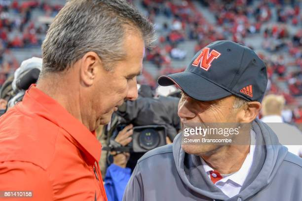 Head coach Urban Meyer of the Ohio State Buckeyes and head coach Mike Riley of the Nebraska Cornhuskers meet before the game at Memorial Stadium on...