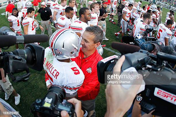 Head coach Urban Meyer of the Ohio State Buckeyes celebrates with Braxton Miller after beating the Michigan State Spartans 17-16 at Spartan Stadium...