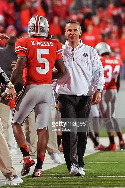 Head Coach Urban Meyer of the Ohio State Buckeyes congratulates quarterback Braxton Miller of the Ohio State Buckeyes after another touchdown against...