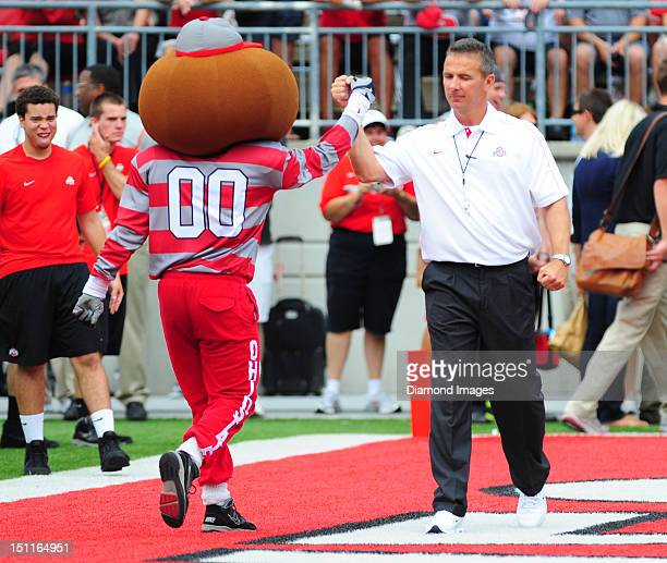 Head coach Urban Meyer of the Ohio State Buckeyes gets a fist bump from mascot Brutus the Buckeye before a game with the Miami Redhawks at Ohio...