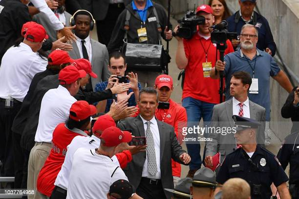 Head Coach Urban Meyer of the Ohio State Buckeyes greets each one of his players as they walk to the locker room at Ohio Stadium before their game...