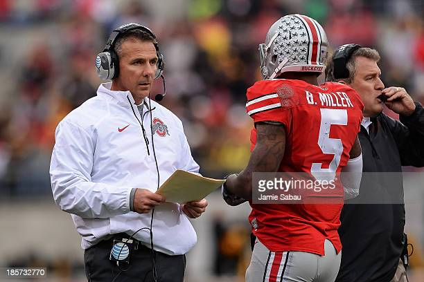 Head Coach Urban Meyer of the Ohio State Buckeyes on the sidelines with quarterback Braxton Miller of the Ohio State Buckeyes during game against the...
