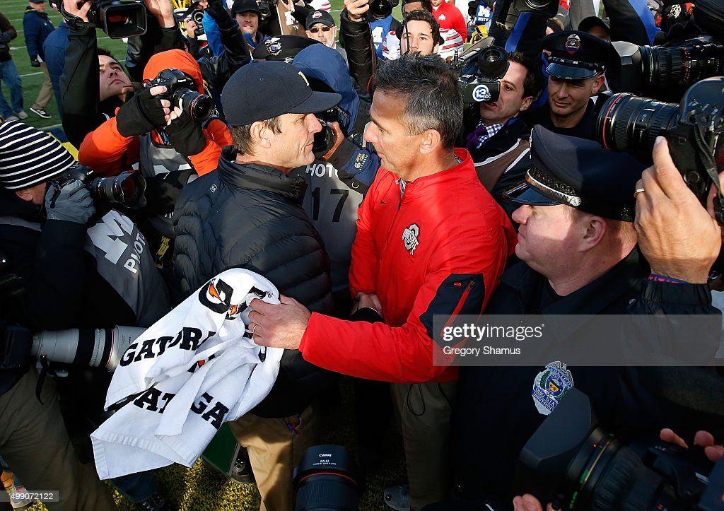 Head coach Urban Meyer of the Ohio State Buckeyes shakes hands with head coach Jim Harbaugh of the Michigan Wolverines after a 42-13 Ohio State win at Michigan Stadium on November 28, 2015 in Ann Arbor, Michigan.