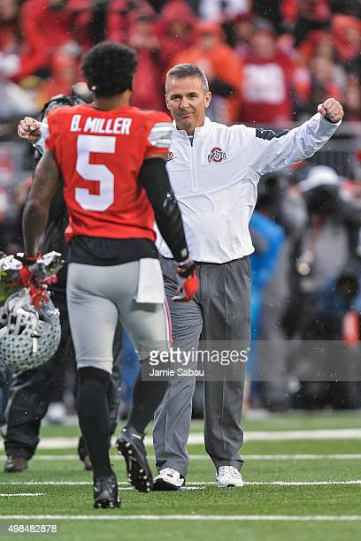 Head Coach Urban Meyer of the Ohio State Buckeyes welcomes Braxton Miller of the Ohio State Buckeyes on to the field during senior day activities...