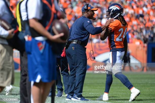 Head coach Vance Joseph talks with Adam Jones of the Denver Broncos during a game against the Seattle Seahawks at Broncos Stadium at Mile High on...