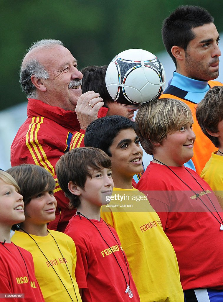 Head coach Vicente del Bosque of Spain balances a football on the head of a boy prior to the start of a training session on May 28, 2012 in Schruns, Austria.