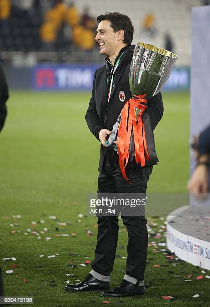 Head coach Vincenzo Montella of AC Milan poses with the trophy after winning the Supercoppa TIM Doha 2016 match between Juventus FC and AC Milan at...