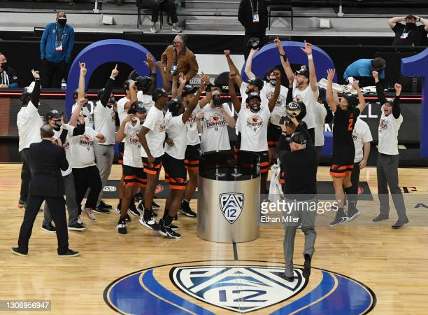 Head coach Wayne Tinkle of the Oregon State Beavers holds up the championship trophy as the team celebrates their 70-68 victory over the Colorado...