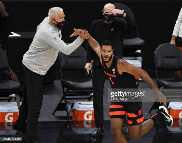 Head coach Wayne Tinkle of the Oregon State Beavers reaches out to celebrate with Maurice Calloo after he hit a 3-pointer against the Oregon Ducks...