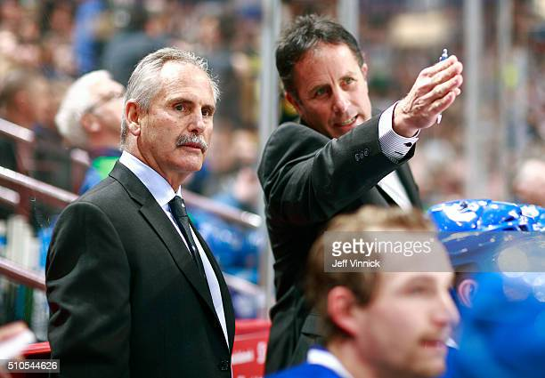 Head coach Willie Dejardins and assistant coach Doug Lidster of the Vancouver Canucks look on from the bench during their NHL game against the...