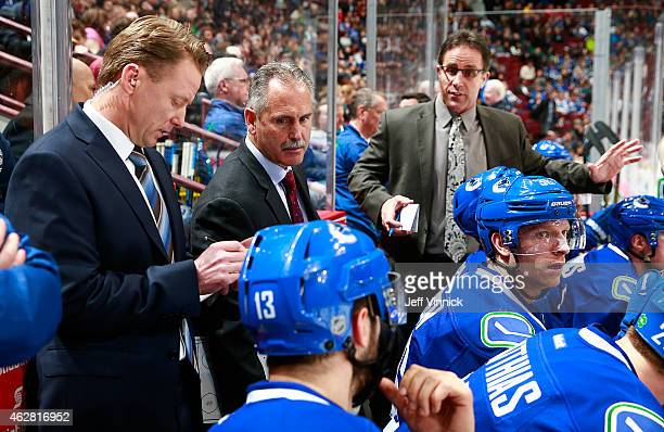 Head coach Willie Desjardins and assistant coaches Doug Lidster and Glen Gulutzan of the Vancouver Canucks talk to players on the bench during their...