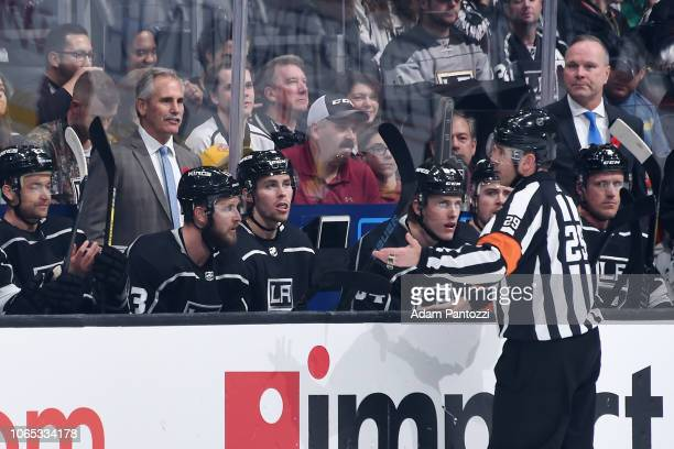 Head coach Willie Desjardins of the Los Angeles Kings talks with referee Ian Walsh talk during the first period of the game against the Minnesota...