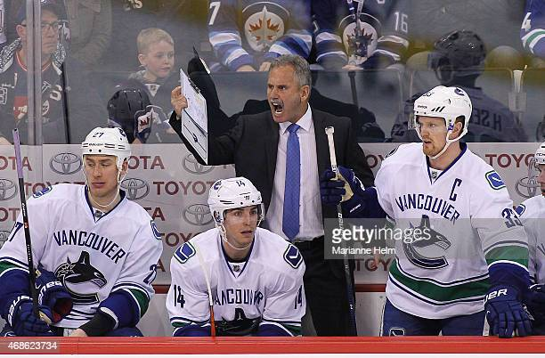Head coach Willie Desjardins of the Vancouver Canucks calls from the bench during third period action in an NHL game against the Winnipeg Jets at the...