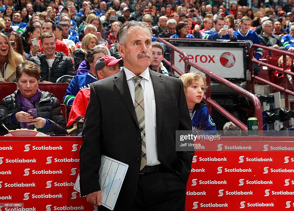 Head coach Willie Desjardins of the Vancouver Canucks looks on from the bench during their NHL game against the Calgary Flames at Rogers Arena January 10, 2015 in Vancouver, British Columbia, Canada. Calgary won 1-0.