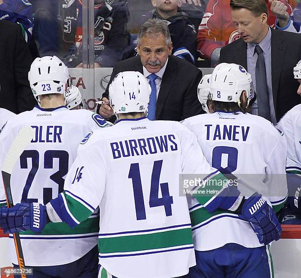 Head coach Willie Desjardins of the Vancouver Canucks talks to his team from the bench during third period action in an NHL game against the Winnipeg...