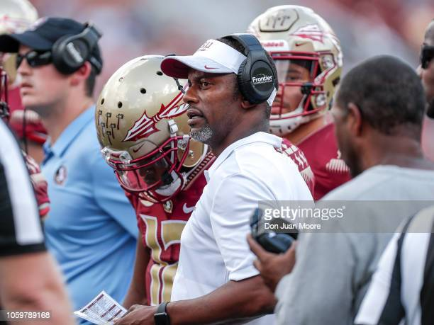 Head Coach Willie Taggart of the Florida State Seminoles talk with Quarterback Deondre Francois during a timeout during the game against the Wake...