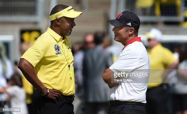 Head coach Willie Taggart of the Oregon Ducks and head coach Mike Riley of the Nebraska Cornhuskers speak before the game at Autzen Stadium on...
