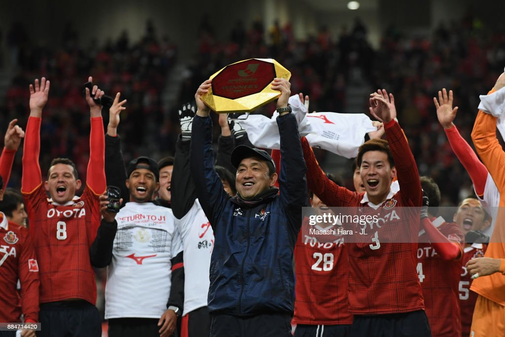 Head coach Yahiro Kazama of Nagoya Grampus lifts the trophy as they celebrate the promotion to the J1 after the J.League J1 Promotion Play-Off Final between Nagoya Grampus and Avispa Fukuoka at Toyota Stadium on December 3, 2017 in Toyota, Aichi, Japan.