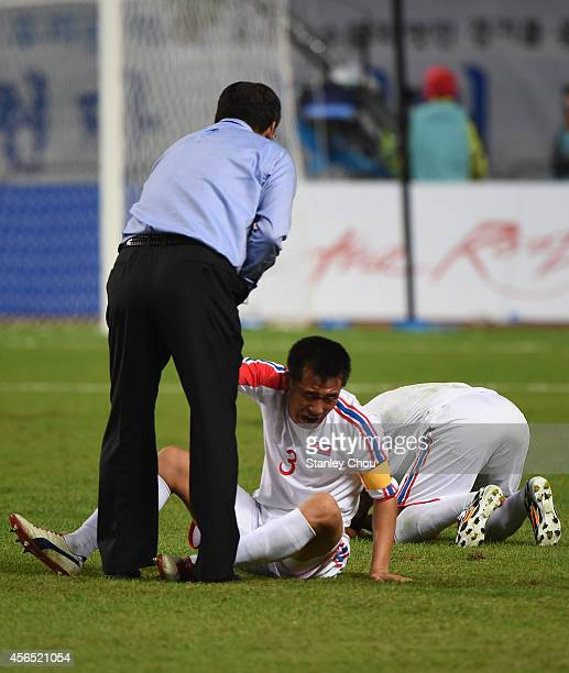 Head coach Yun Jongsu of North Korea consoles Jang Songhyok after the 01 defeat in the Football Men's Gold Medal match between South Korea and North...