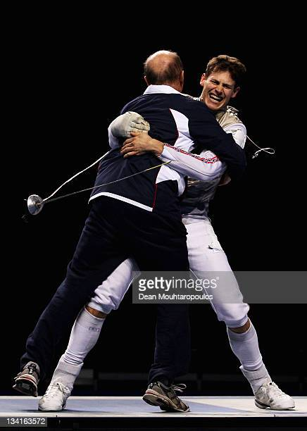 Head Coach Ziemek Wojiechowski and Richard Kruse celebrate after their gold medal win in the Men's Foil Team Event at the Fencing Invitational part...