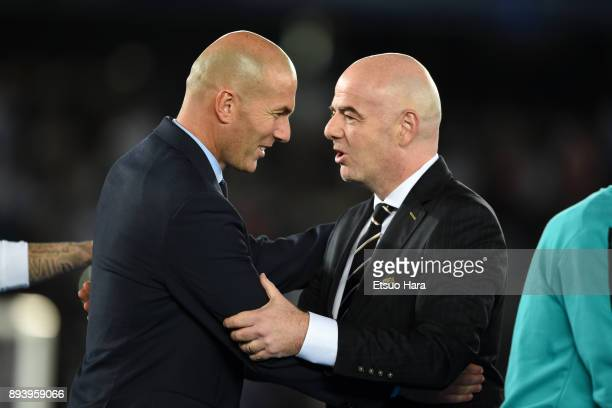 Head coach Zinedine Zidane of Real Madrid celebrates with FIFA president Gianni Infantino during the medal ceremony after the FIFA Club World Cup UAE...