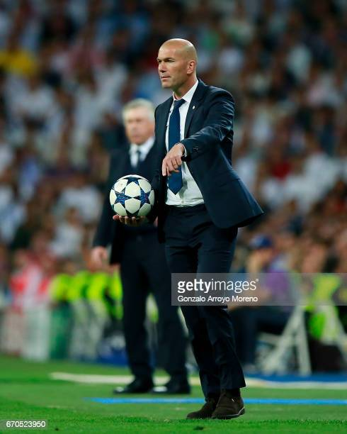 Head coach Zinedine Zidane of Real Madrid CF holds the ball ahead coach Carlo Ancelotti of Bayern Muenchen during the UEFA Champions League Quarter...