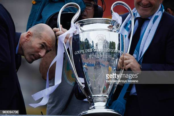 Head coach Zinedine Zidane of Real Madrid CF looks to the trophy as he celebrates with his team at Cibeles Square a day after winning their 13th...