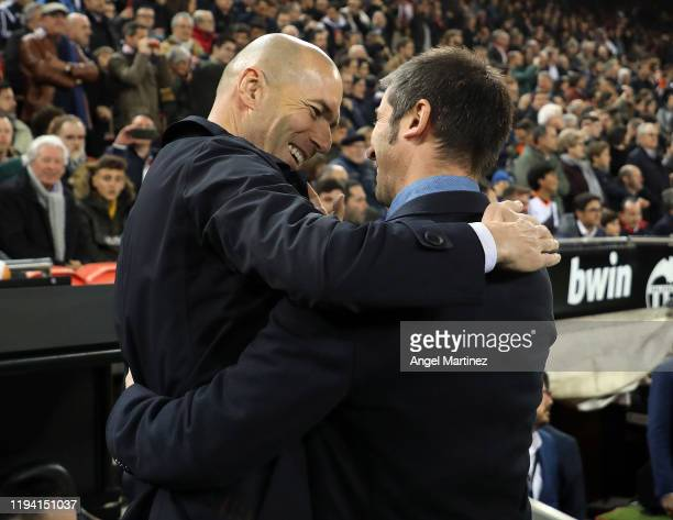 Head coach Zinedine Zidane of Real Madrid embraces head coach Albert Celades of Valencia the Liga match between Valencia CF and Real Madrid CF at...