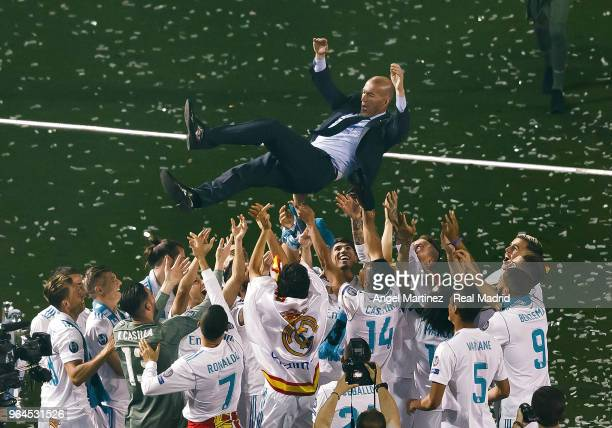 Head coach Zinedine Zidane of Real Madrid is thrown in the air by his players during celebrations at the Santiago Bernabeu stadium following their...