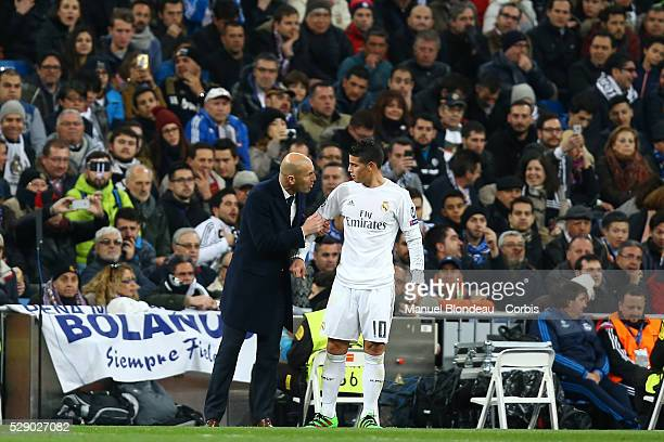 Head Coach Zinedine Zidane of Real Madrid talks to James Rodriguez during the UEFA Champions League round of 16 2nd leg football match between Real...